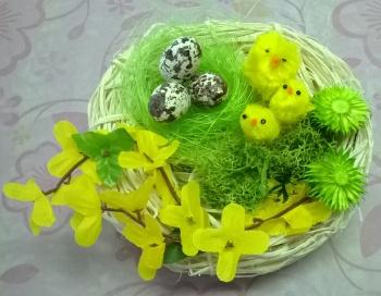 Dekorace z proutěného základu ve tvaru ptaččího hnízda zdobená kuřátky, vajíčky, zlatým deštěm, což vše vyjadřuje jaro.